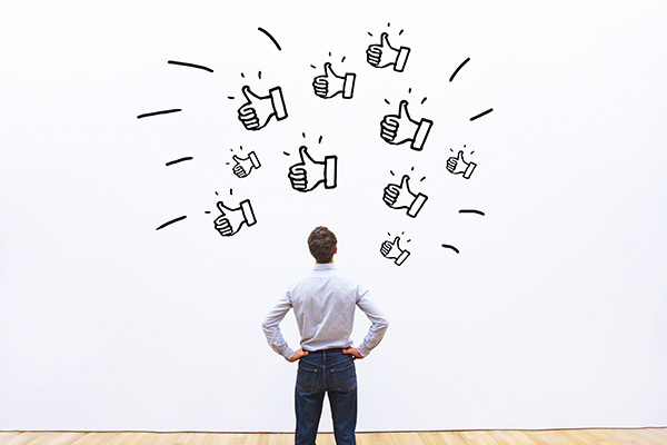 Man standing before a wall covered with illustrations of thumbs up