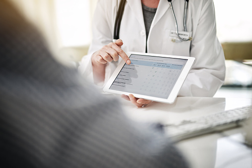 Dentist reviewing digital patient forms on a tablet with a patient
