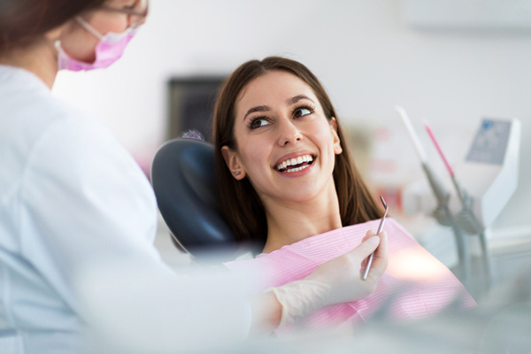 Woman smiling in a dental chair learning about the dental services at Martin Periodontics in Mason & North Cincinnati, OH